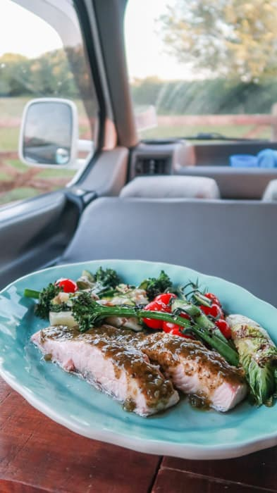 turquoise plate with salmon and veggies on a table in a campervan