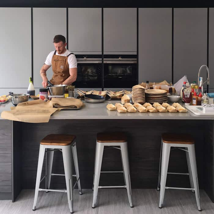 modern stylish kitchen with stools, work surface and chef preparing food in the background