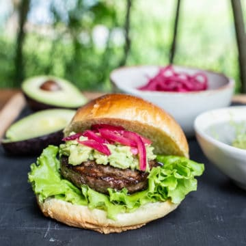garden table scene with burger in brioche bun, mashed avocado and pickled red onions and various ingredients in background