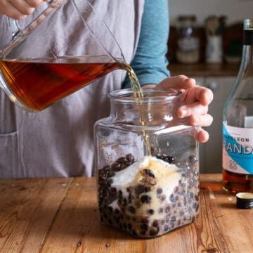 woman in grey pouring brandy from a glass jug into a big glass jar of blackcurrants