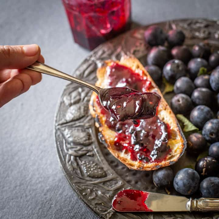 a spoon of wild sloe and blackberry jam held over a piece of toast and damsons on a pewter plate