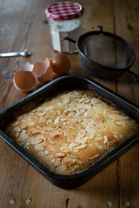 black square baking tin filled with golden brown almond cake surrounded by broken eggs shells and baking mess