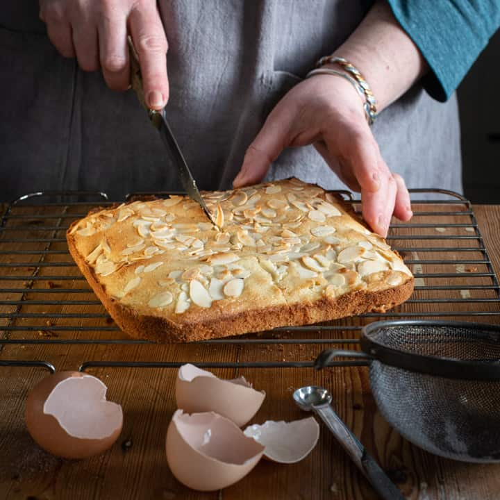 womans hands cutting a homemade tray bake cake on a wooden kitchen counter