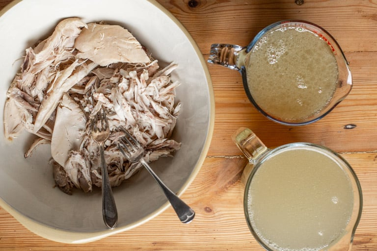 wooden background with shredded slow cooker whole chicken and 2 jugs of homemade chicken stock