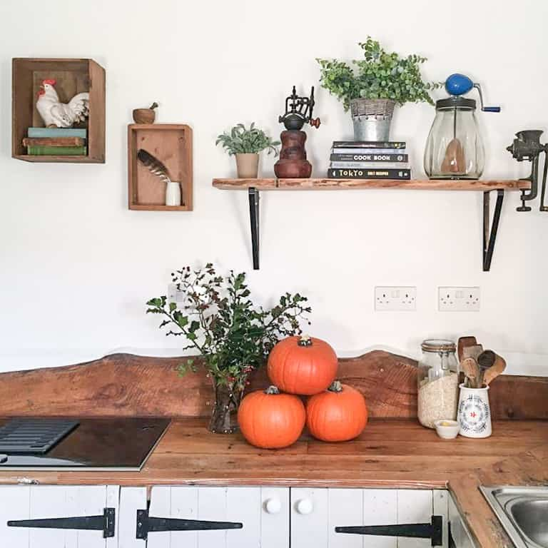 rustic style kitchen with rustic kithchenalia and a wooden counter with three large orange pumpkins ready to make dairy free pumpkin soup