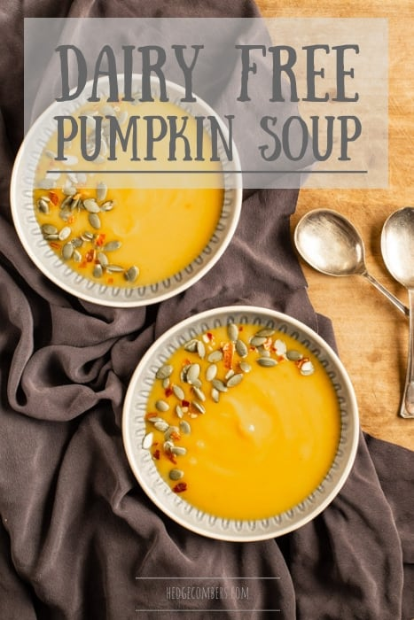 wooden background with two bowl of dairy free pumpkin soup sprinkled with pumpkin seeds and chilli flakes