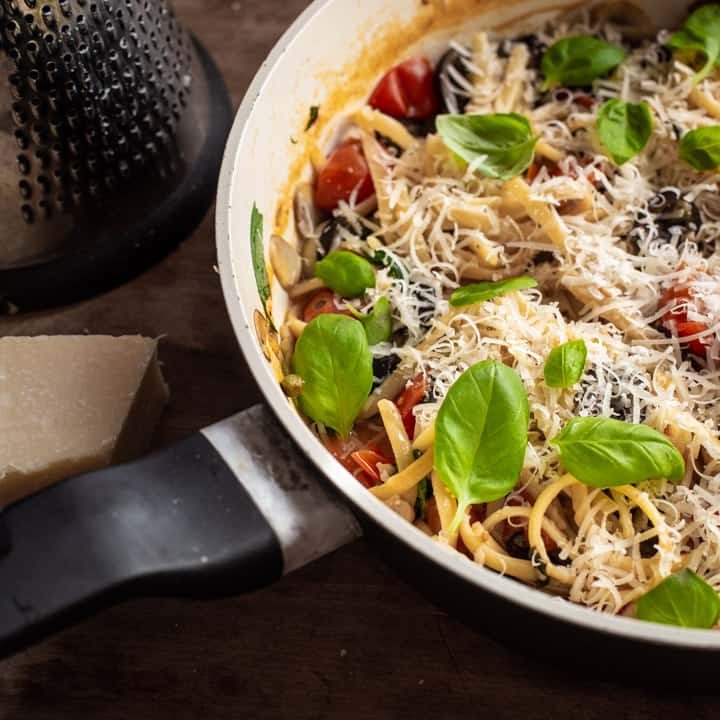 wooden background with black and white saute pan filled with one pot veggie pasta, fresh parmesan and basil leaves