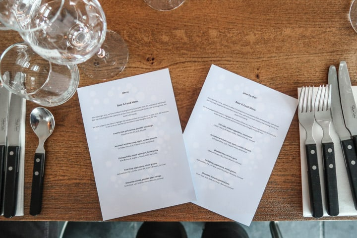 wooden table with silverware, glasses and two personalised menus