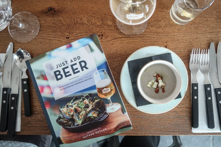wooden table with silverware and a copy of Just Add Beer cookbook at the Padstow Christmas Festival