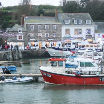 harbour shot at padstow christmas festvival with fishing boats, fairy lights and crowds in teh background