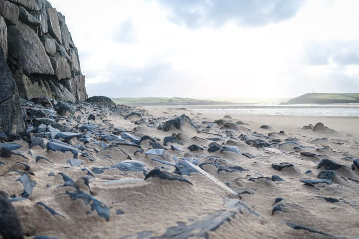 beach scene with wind whipping sand over pebbles at Rock, Cornwall