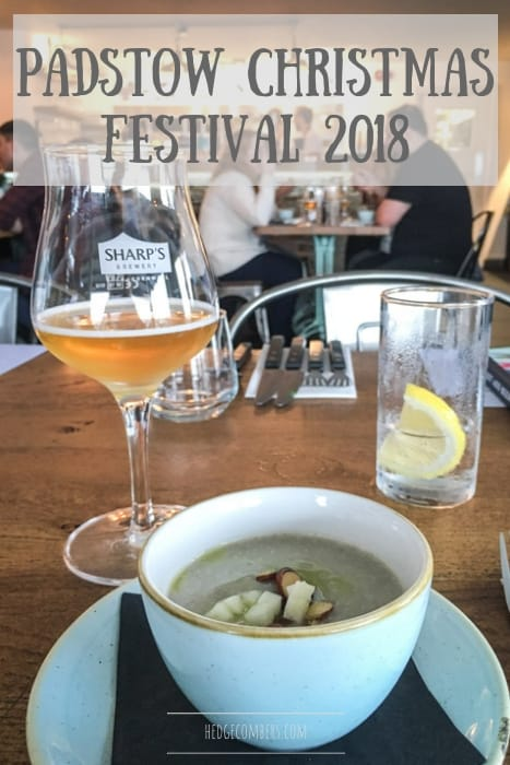 busy restaurant scene at the Padstow christmas festival with white bowl of green soup, glass of beer and glass of lemon water
