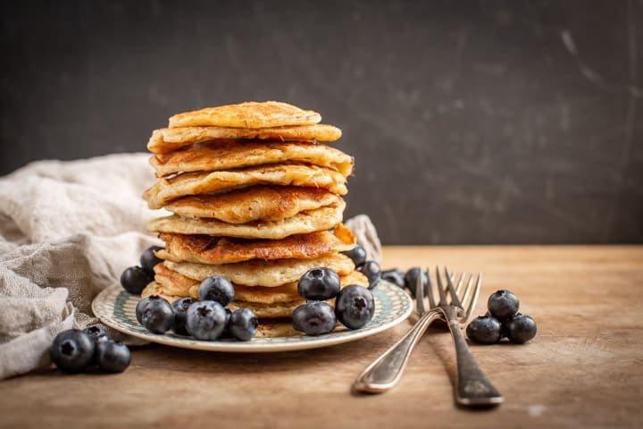 black background with stack of eggless pancakes with blueberries