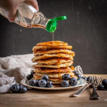 black background with stack of eggless pancakes with blueberries and maple syrup being poured over