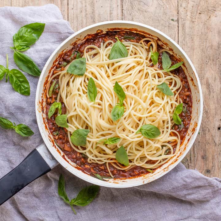 wooden background with white pan with vegan spaghetti bolognese piled up and scattered with fresh basil leaves