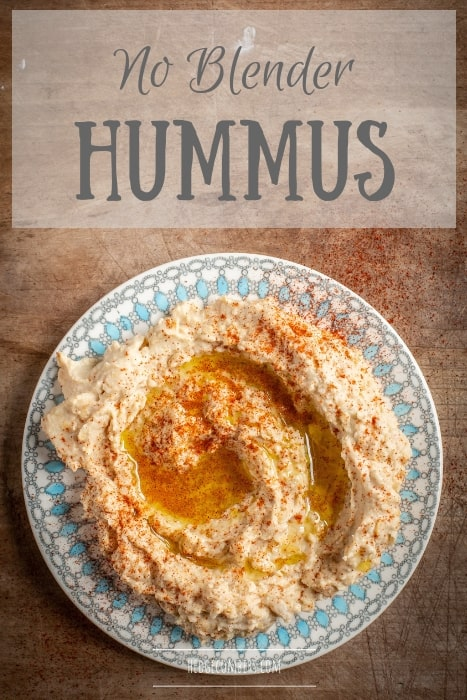 wooden bakground with pretty plate filled with homemade hummus drizzled with olive oil and smoked paprika