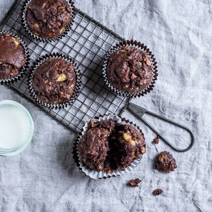 neutral background with 5 banana chocolate muffins and a glass of milk