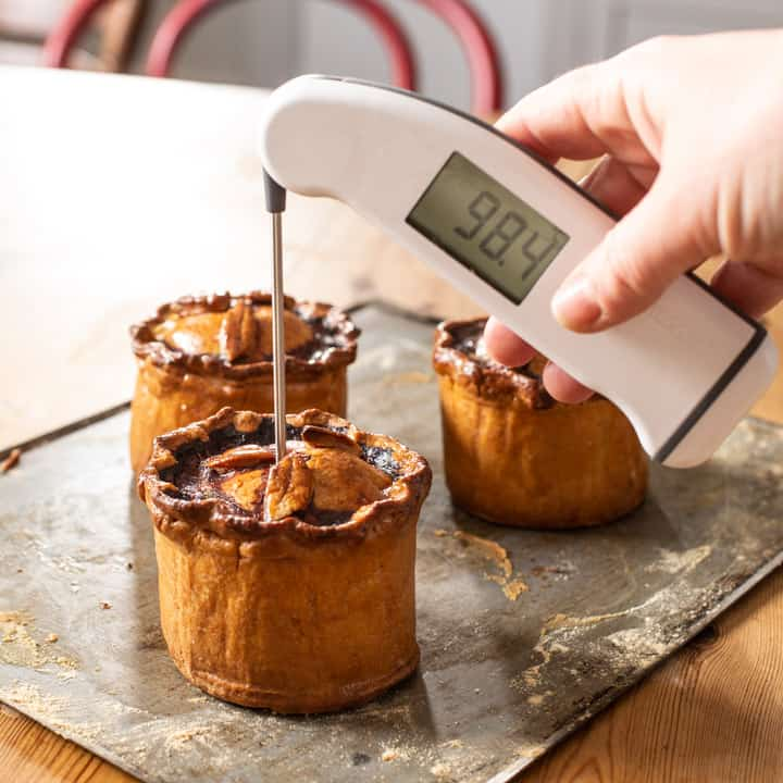 3 handmade British pork pies being tasted for their internal temperature with a white digital thermometer