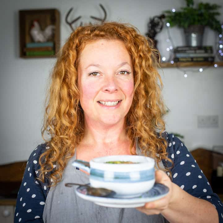 Jane Sarchet with red, curly hair holding bowl of slow cooked irish stew