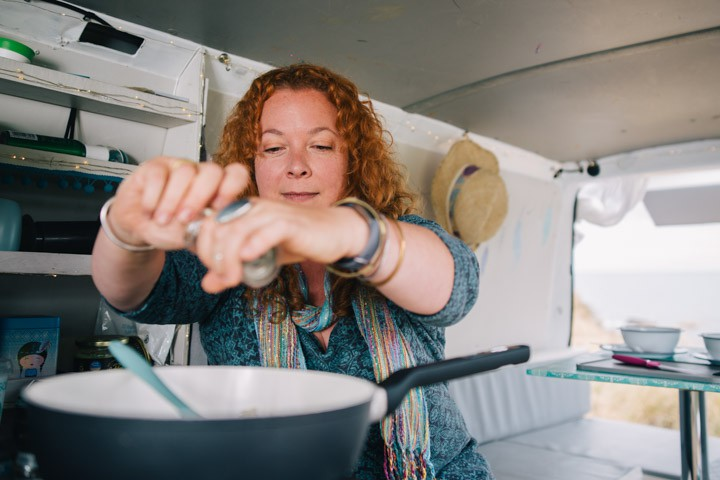 Jane Sarchet grinding a pepper mill over a saute pan in her VW campervan