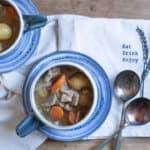 white cloth with blue blue filled with slow cooker Irish stew and 2 spoons