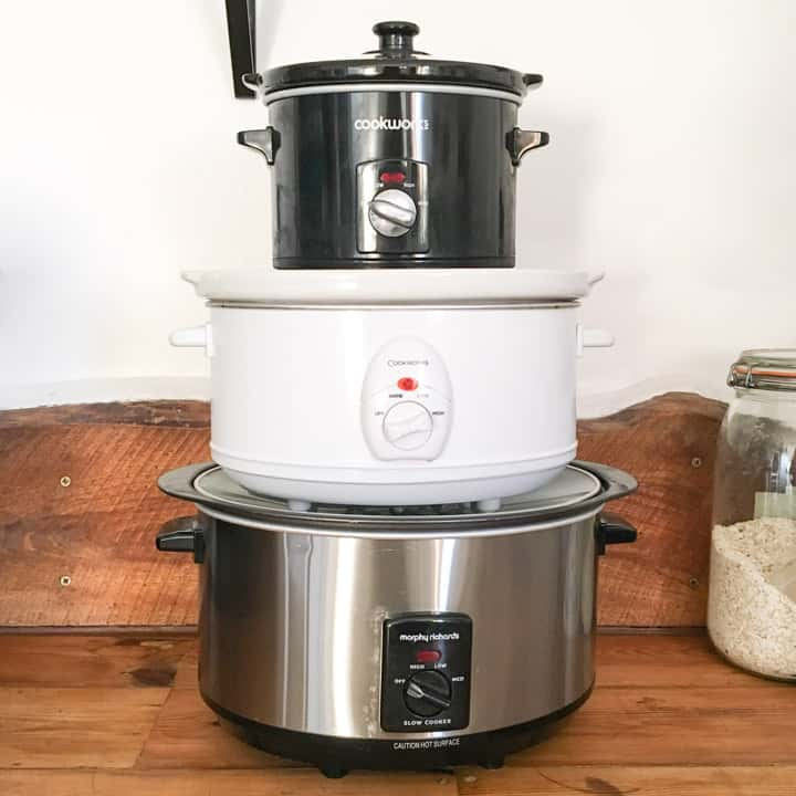 wooden kitchen surface with 3 slow cookers of different sizes stacked up