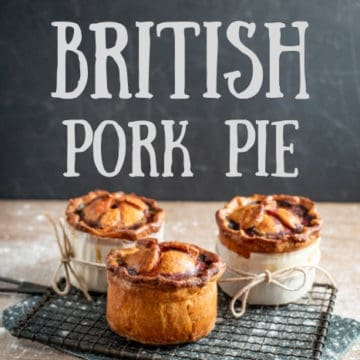 3 handmade British pork pies cooling on a wire rack over a wooden board