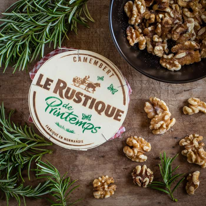 wooden board scatted with walnuts sprigs of rosemary and a round wooden tub of Le Rustique Camembert cheese