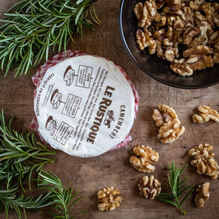 wooden board scatted with walnuts sprigs of rosemary and a package of fresh Camembert cheese