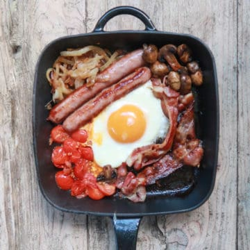 wooden background with cast iron breakfast skillet filled with breakfast foods like sausages, bacon, eggs, mushrooms etc