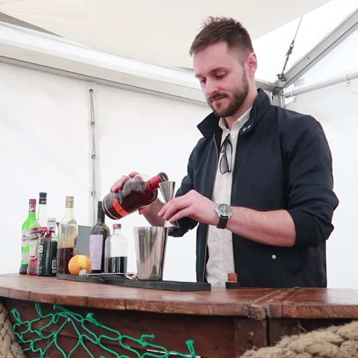 Bar tender pouring spirits into a cocktail shaker at the Porthleven Food Festival 2019