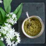 slate background with bowl of homemade Ramsons Pesto and some ramson flowers