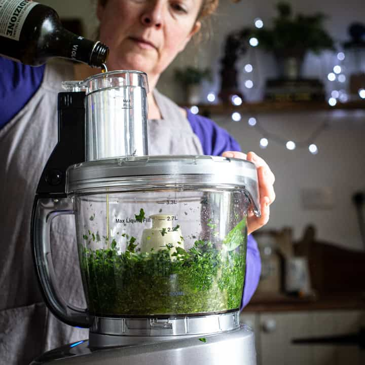 woman in grey pouring olive oil into a food processor to make fresh pesto
