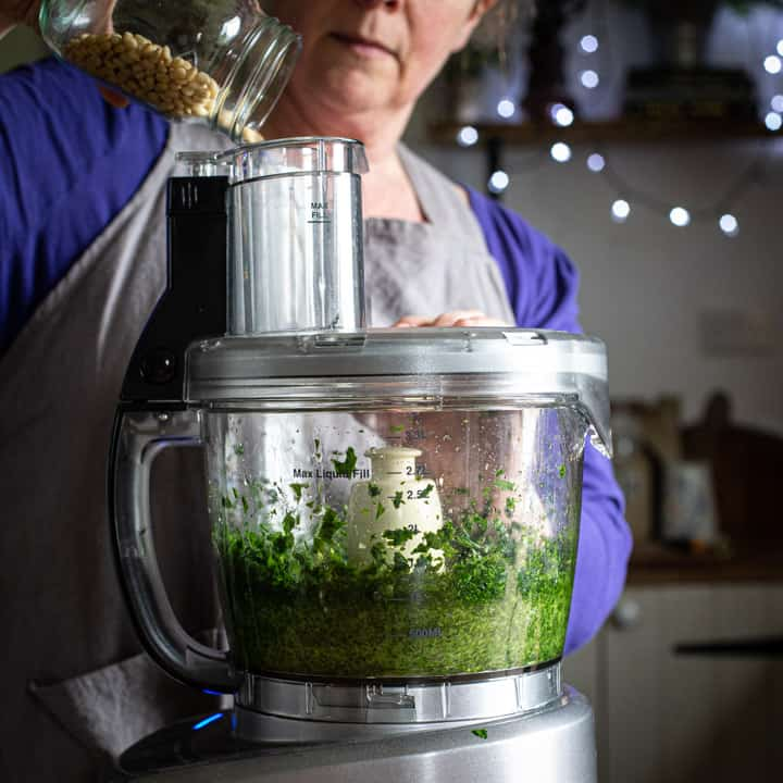 woman in grey pouring nuts into a food processor to make pesto