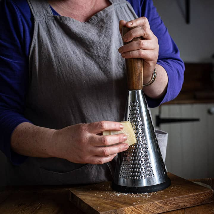 woman in grey grating a block of parmesan cheese onto a wooden board