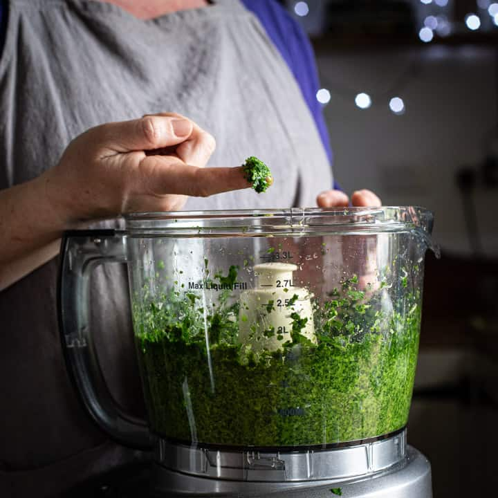 woman in a kitchen taking a small amount of homemade pesto on her finger to taste
