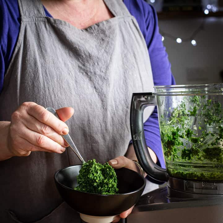woman spooning wild garlic pesto into a small black bowl from a food processor