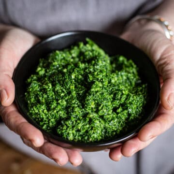 woman in grey holding a black bowl or bright green homemade ramson pesto