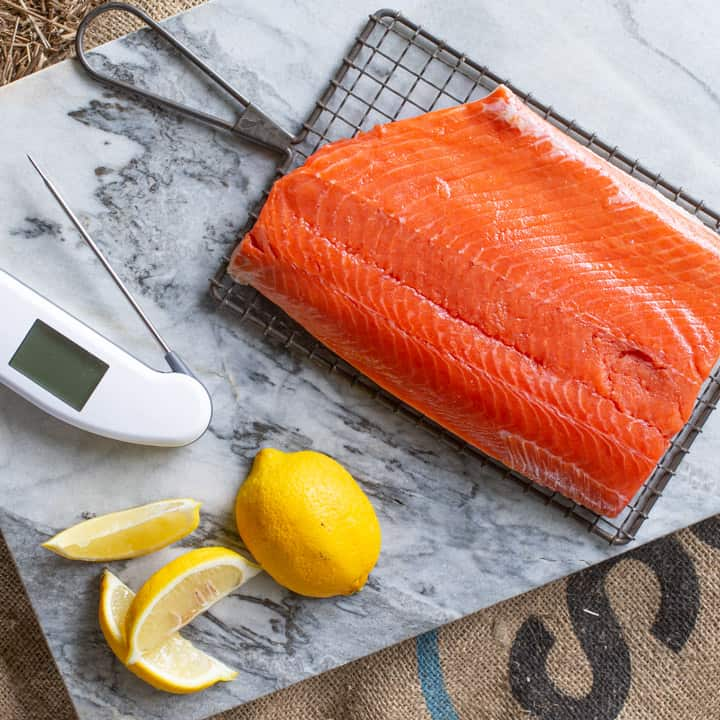 Piece of salmon prepared for smoking on marble chopping board with fresh lemon