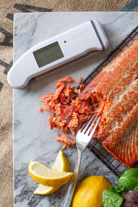 marble chopping board with a fork, hot smoked salmon, lemon wedges and digital thermometer