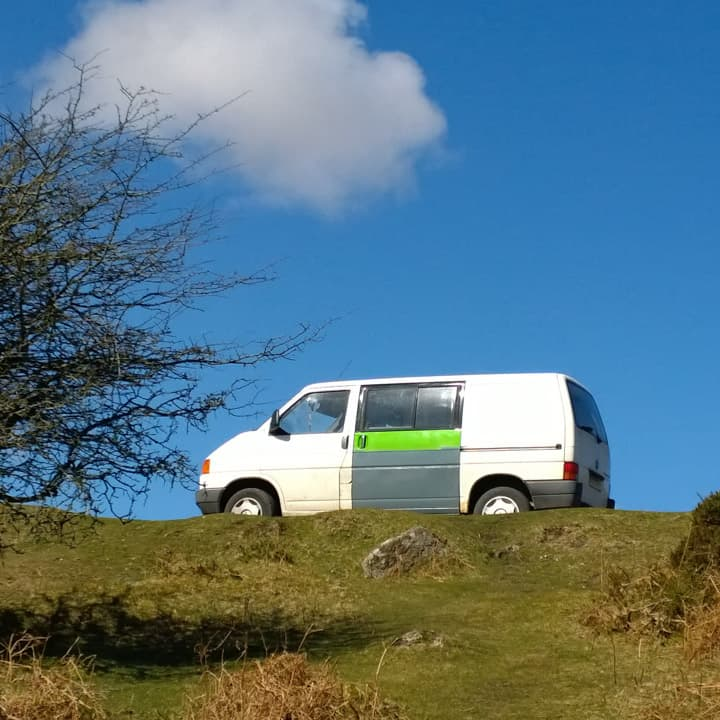 scruffy old VW T4 van with white, green and grey bodywork against a blue sky