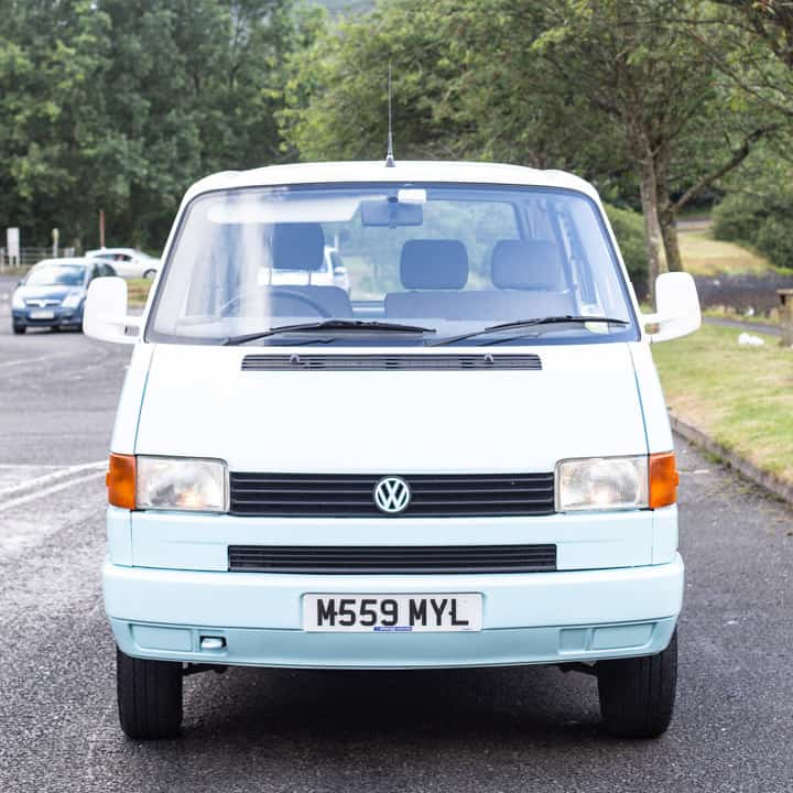 head on shot of a pale blue and white VW T4 campervan parked in a car park