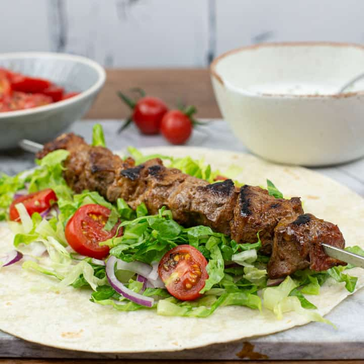 marble board with bbq lamb kebabs, flatbread and fresh salads