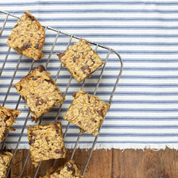 healthy banana flapjack squares on a metal cooling rack on top of stripey fabric