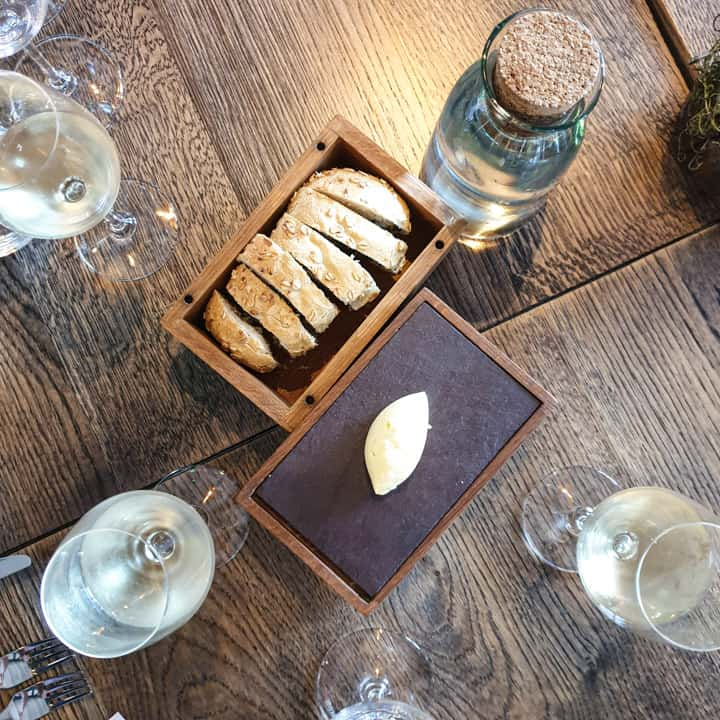 wooden table with box of homemade laverbread bread and whipped butter in wooden box