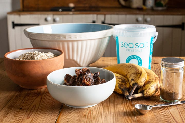 a rustic kitchen counter with verious bowls of baking supplies ready to make healthy flapjacks