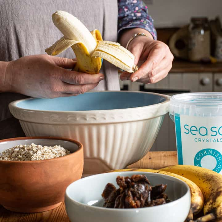 woman in grey peeling a banana in a kitchen scene surrounded with baking ingredients