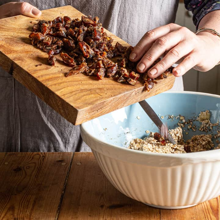 woman in grey tipping chopped dates from a wooden board into a blue and white mixing bowl