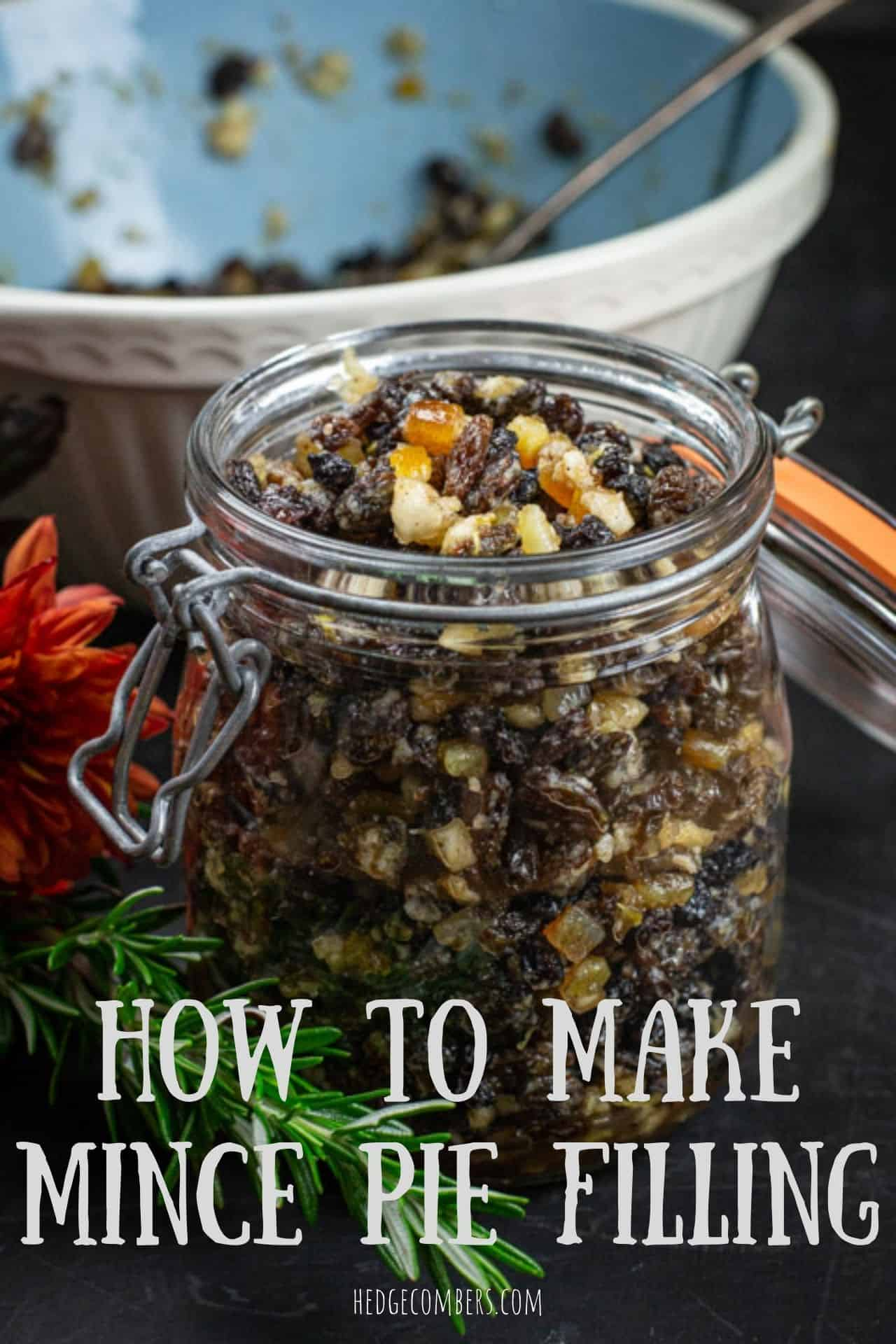 glass jar filled with fruity mincemeat filling on a kitchen counter with baking mess around