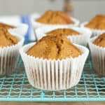 pumpkin spice muffins in white paper wrapper on a pale blue wire cooling rack